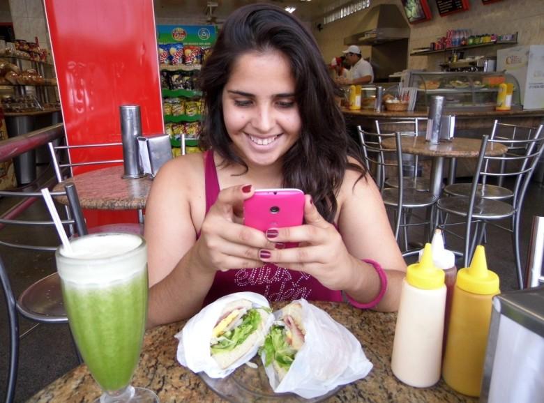 A surubinense Mayara Cabral, esquecendo de se alimentar para mexer no seu adorado smartphone   Foto: ilustração